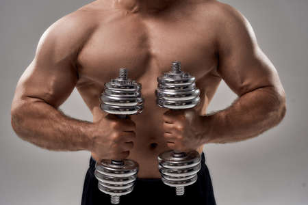 Young muscular caucasian male athlete lifting dumbbells 免版税图像 - 159139314