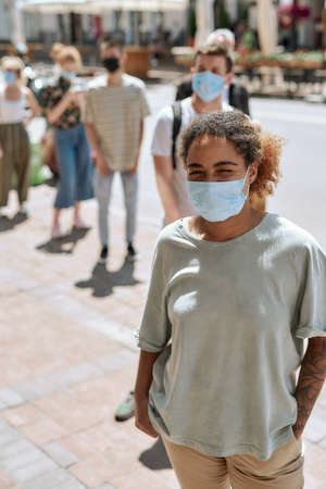Young african american woman wearing mask standing with other people in line, respecting social distancing to enter takeout restaurant during coronavirus lockdown