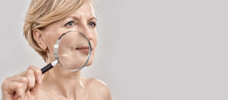 Close up portrait of attractive middle aged woman looking aside, holding a magnifying glass and showing her wrinkles, posing isolated over grey background 免版税图像 - 159139317
