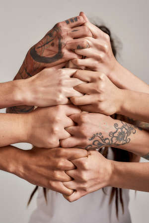 Diverse women holding their hands on top of each other closed together like a lock over grey background. Concept of racial unity and relations in society