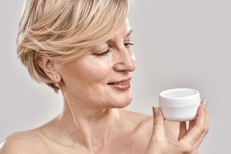 Close up portrait of beautiful middle aged woman holding, looking at moisturizing cream jar while posing isolated over grey background