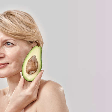 Cropped portait of beautiful middle aged woman looking aside while holding half of a ripe delicious avocado near her face, posing isolated over grey background