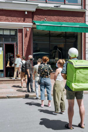Full length shot of people waiting, standing in line, respecting social distancing to collect their orders, purchases from the pickup point during coronavirus lockdown