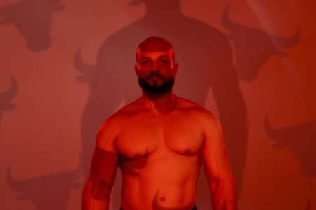 Young muscular caucasian man posing on orange background