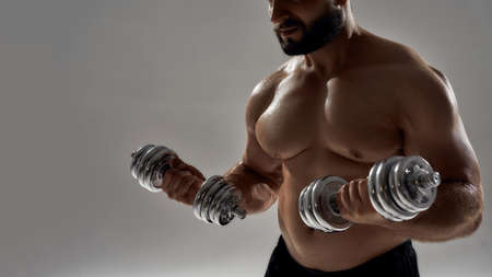 Muscular caucasian bodybuilder exercising with dumbbells 免版税图像 - 159139324