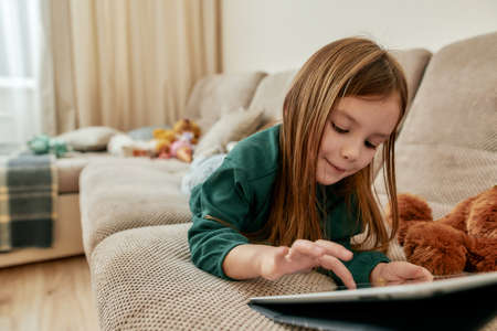 A cute little girl enjoy playing games on her tablet while lying on her stomach on a sofa 版權商用圖片