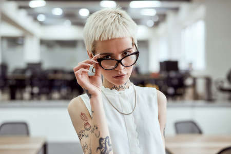 Young and succesful. Portrait of confident blonde tattooed businesswoman adjusting her eyeglasses and looking at camera while standing in the modern working space 免版税图像 - 159145040