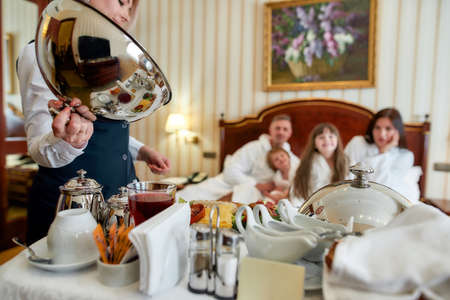 Thousand flavors in one place. Caucasian parents and two kids waiting for breakfast delivered by waitress in unifrom in luxurious hotel room. Family, travel, resort, room service concept