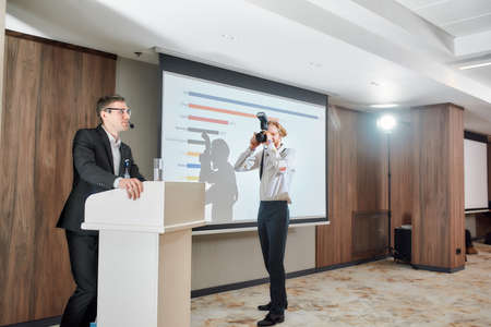 Capture the moment. Full-length shot of photographer taking photo of male speaker giving a talk on corporate business meeting at the conference hall Stock fotó
