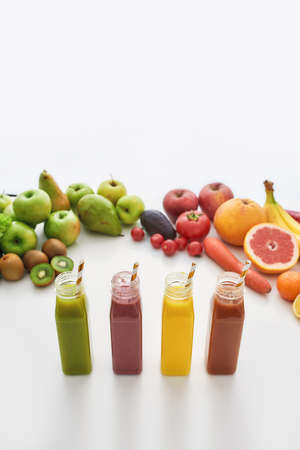 Composition of healthy detox juices and smoothies in bottles with paper straws, Various colorful fruits and vegetables isolated over white background