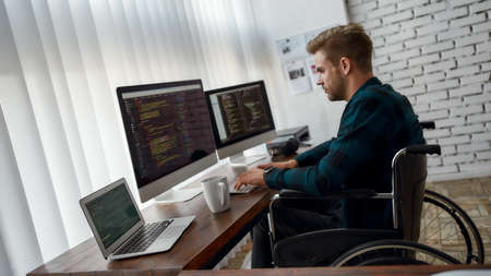 Writing computer program. Side view of young professional web developer in a wheelchair writing program code on multiple computer screens while sitting at his workplace in the modern office