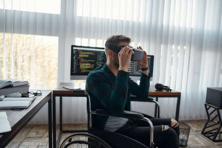 Young male web developer in a wheelchair wearing virtual reality glasses while working at his workplace in modern office. Multiple computer screens with program code 免版税图像 - 159316851