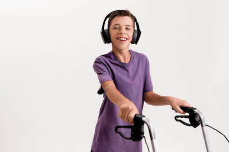 Portrait of happy teenaged disabled boy with cerebral palsy in headphones smiling at camera, taking steps with his walker isolated over white background