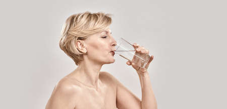 Attractive middle aged woman drinking fresh cold water from a glass while posing isolated over grey background