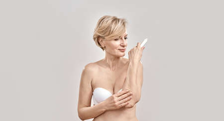 Attractive middle aged woman applying exfoliating moisturizing cream on dry elbow skin while posing isolated over grey background