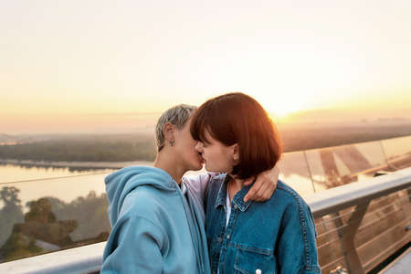 Young passionate lesbian couple kissing outdoors, Two women enjoying romantic moments together at sunrise 免版税图像
