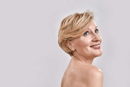 Portrait of beautiful naked middle aged woman smiling, looking up while posing isolated against grey background. Beauty, skincare concept
