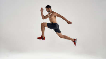 Young handsome caucasian male runner jumping high