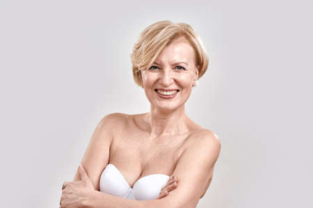 Portrait of beautiful middle aged woman in white bra smiling at camera while posing isolated against grey background. Beauty concept 免版税图像