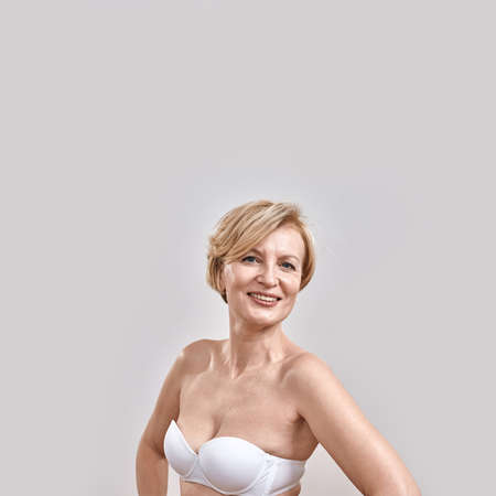 Portrait of beautiful middle aged woman in white bra smiling at camera, posing isolated against grey background