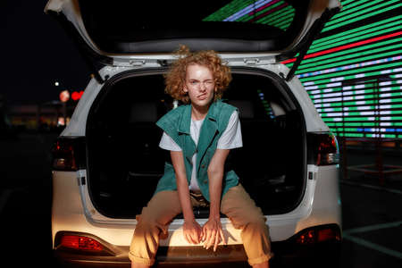 An artistic good-looking redhead young woman with freckles looking into a camera winking her eye while sitting inside of an opened car trunk with a led screen behind