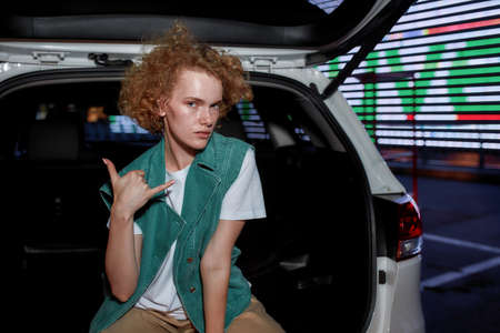 A casually dressed redhead young woman with freckles looking into a camera making a call me gesture while sitting inside of an opened car trunk with a led screen behind