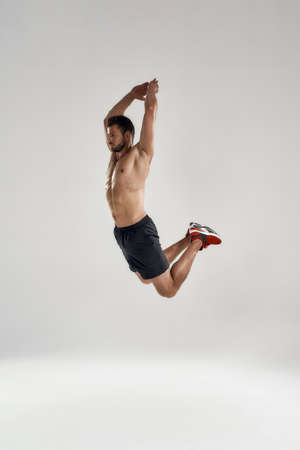 Young male athlete in high sideway jump with raised hands 版權商用圖片