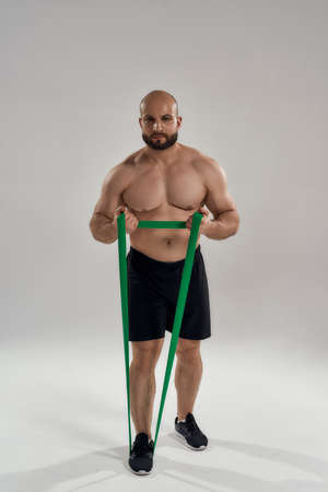Young muscular caucasian bodybuilder with elastic band