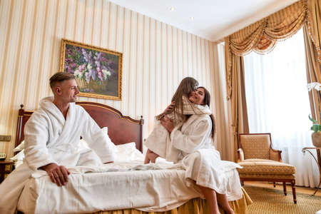 Enjoy the stay. Caucasian parents and daughter in white bathrobes relaxing and spending morning together. They are sitting on the bed in luxurious hotel room. Family, travel, resort, vacation concept 免版税图像