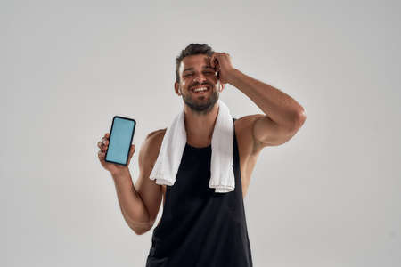 Smiling young handsome caucasian sportsman demonstrating smartphone 免版税图像
