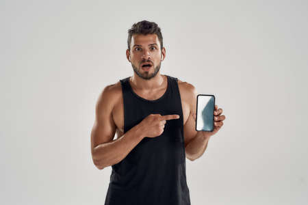 Young muscular caucasian athlete pointing into smartphone screen 免版税图像