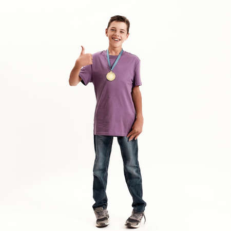 Full length shot of teenaged disabled boy with cerebral palsy wearing gold medal, smiling and showing thumbs up at camera, standing isolated over white background 免版税图像