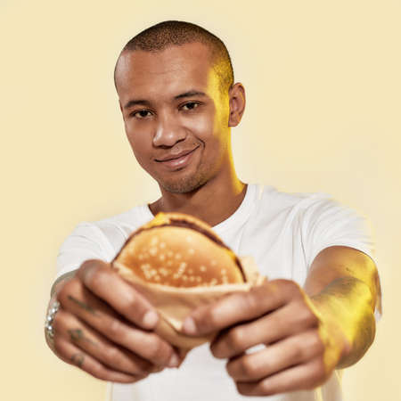 Eating food. A dark-skinned male with tattoos holding a burger in hands while smiling and looking into a camera