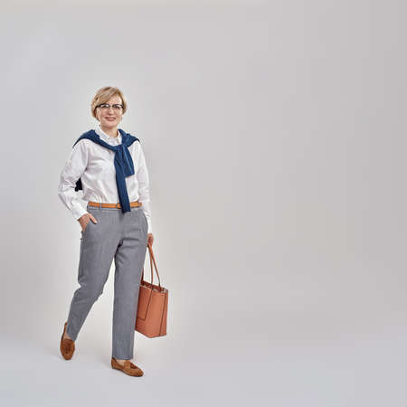 Full length shot of elegant middle aged caucasian woman wearing business attire and glasses smiling at camera while posing, standing with handbag isolated over grey background