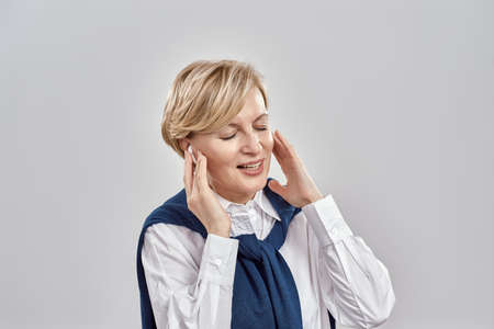 Portrait of elegant middle aged caucasian woman wearing business attire, adjusting her earbuds, enjoying the sound with eyes closed while posing isolated over grey background