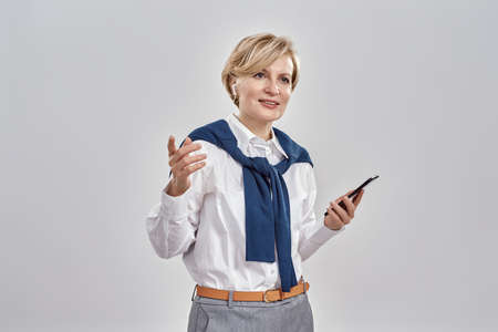 Portrait of elegant middle aged caucasian woman wearing business attire and earphones holding smartphone, smiling away while standing isolated over grey background