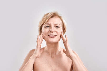 Portrait of beautiful middle aged woman satisfied with skincare treatment. She is touching her face, looking at camera while posing isolated against grey background. Beauty concept 免版税图像