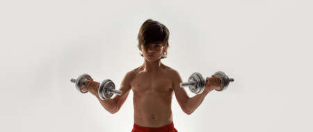 Little sportive boy child with muscular body looking focused at camera, lifting weights while standing isolated over white background