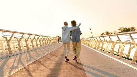 Full length shot of lesbian couple hugging, walking on the bridge and watching the sunrise together