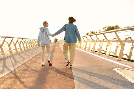 Full length shot of happy lesbian couple holding hands, walking on the bridge and watching the sunrise together. Homosexuality, LGBT and love concept