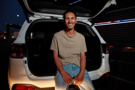 A commonly dressed dark-skinned young latina man with a piercing smiling looking into a camera sitting in an opened car trunk outside on a parking site with a led screen behind him 免版税图像