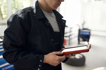 Young caucasian man standing with tablet at car service 免版税图像