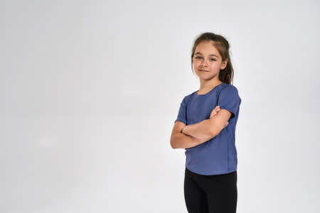 Little sportive girl child in sportswear looking at camera, while standing with arms crossed isolated over white background