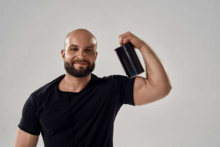Smiling young caucasian bodybuilder holding sport nutrition bottle on biceps