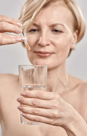 Close up of hand of attractive middle aged woman holding dropper with medication and glass isolated over grey background