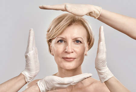 Portrait of attractive middle aged woman looking at camera. Beautician creating a frame around female face with hands in gloves isolated against grey background