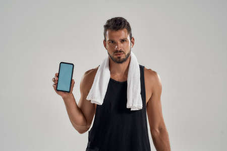 Young muscular caucasian man after training holding smartphone