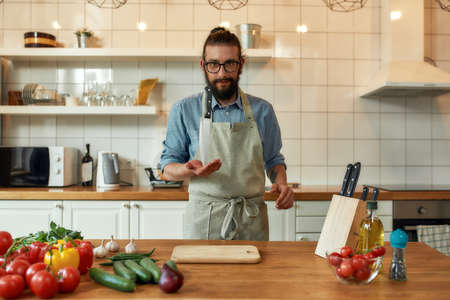 Young man, Italian cook in apron looking at camera, holding knife the tip of the blade while preparing healthy meal with vegetables in the kitchen. Cooking at home concept
