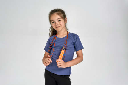 Little sportive girl child in sportswear looking at camera, standing with jump rope while posing isolated over white background 免版税图像