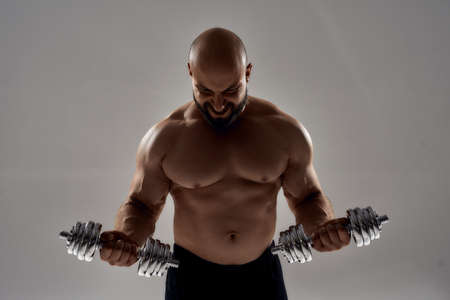Blacked figure of young caucasian bodybuilder with dumbbells